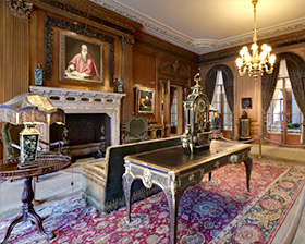 photo of Living Hall gallery in Frick collection with fireplace, couch, table, lamps, paintings